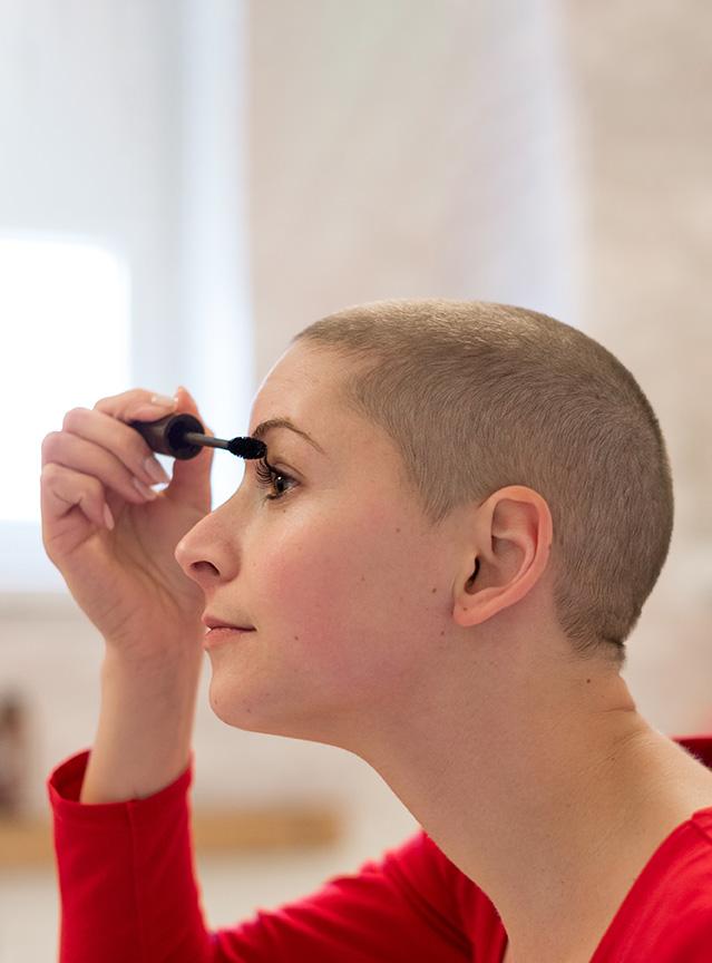 Cacer survivor applying makeup